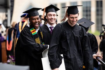 Graduating seniors smile and laugh during the 2018 Undergraduate Commencement ceremony in O'Shaughnessy Stadium on May 18, 2018 in St. Paul.
