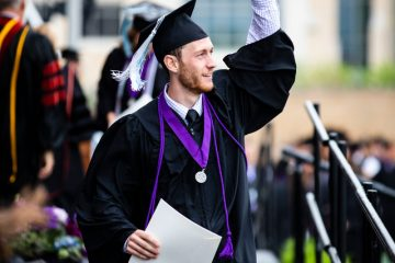 A graduating senior raises and arm in celebration after receiving his degree during the 2018 Undergraduate Commencement ceremony in O'Shaughnessy Stadium on May 18, 2018 in St. Paul.