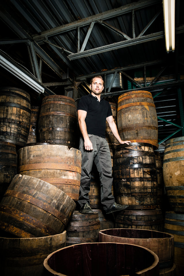 Jason Utgaard stands on old whiskey barrels at BarHomeDesigns in Salt Lake City, Utah. Jason Utgaard, '07 Entrepreneurship, founded The Spotted Door, an online retailer that sells recycled and reclaimed products. BarHomeDesign supplies The Spotted Door with furniture made from repurposed whiskey Barrels.