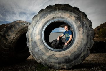Jason Utgaard poses for a portrait in a large tire at a rubber recycling facility in Salt Lake City, Utah, on April 19, 2018. Jason Utgaard, '07 Entrepreneurship, founded The Spotted Door, an online retailer that sells recycled and reclaimed products.
