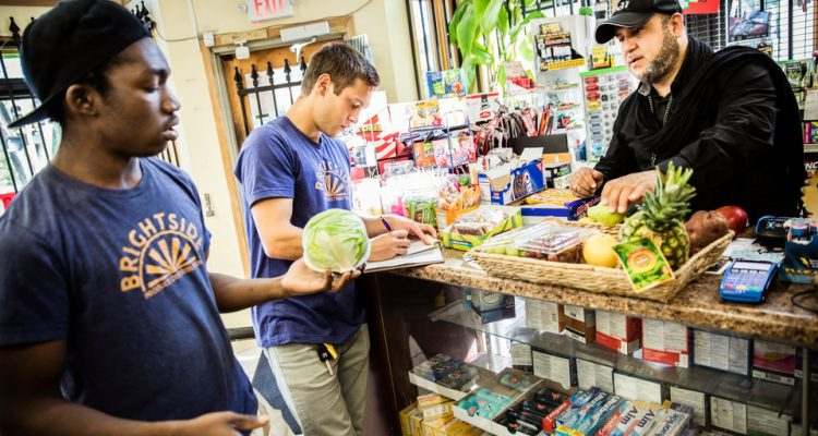 BrightSide employee Steven Fuller, left, and St. Thomas student Ben Kachian (Biology), center, talk with Ahmed, owner of North Side Food Market, while making weekend deliveries to neighborhood stores for BrightSide Produce in Minneapolis on September 30, 2017. BrightSide, a project conceived at St. Thomas and run with the help of students, brings healthy food (some of which comes from the St. Thomas stewardship garden) to underserved communities.