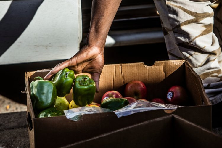 BrightSide employee Steven Fuller drops peppers into a green box while making weekend deliveries to neighborhood stores for BrightSide Produce in Minneapolis.