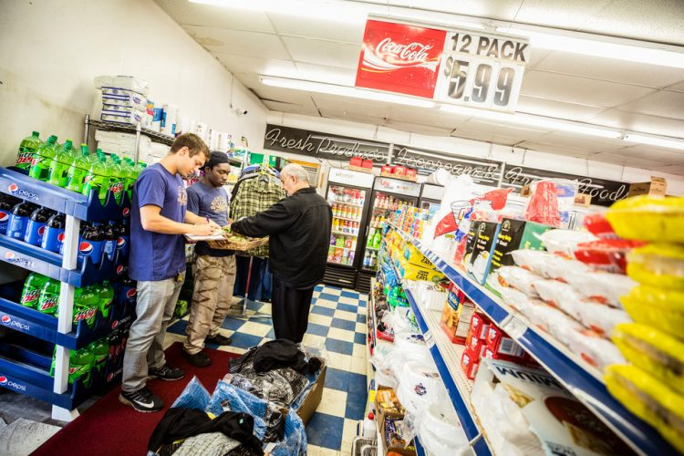 St. Thomas student Ben Kachian (Biology), left, and BrightSide Produce employee Steven Fuller, middle, talk with a store owner while making weekend deliveries to neighborhood stores for BrightSide Produce in Minneapolis on September 30, 2017. BrightSide, a project conceived at St. Thomas and run with the help of students, brings healthy food (some of which comes from the St. Thomas stewardship garden) to underserved communities.